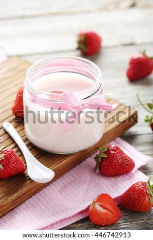Strawberry yogurt in glass on wooden table