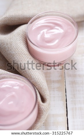strawberry yogurt in glass with cloth place on white wooden background. pink yogurt. pink yoghurt, strawberry yoghurt.