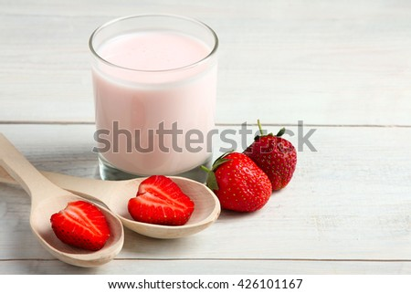 Strawberry yogurt with berries on wooden background