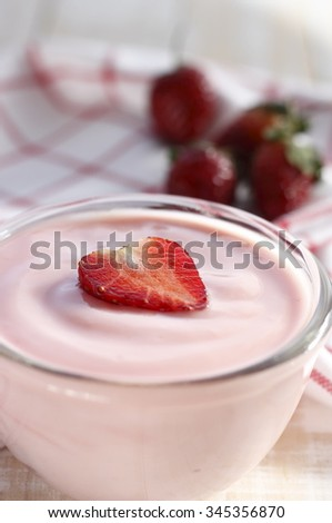 strawberry yogurt with fresh strawberry in heart-like formed on wooden white background. strawberry yoghurt. pink yogurt. strawberry in strawberry yogurt. heart in yogurt. heart. valentine 's day.