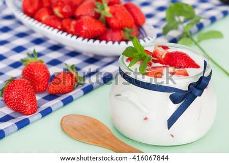 Strawberry yogurt with wooden spoon - stock photo
