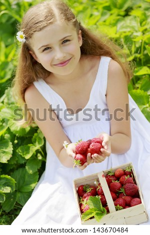 Strawberry - young girl with picked strawberries in the garden - stock photo