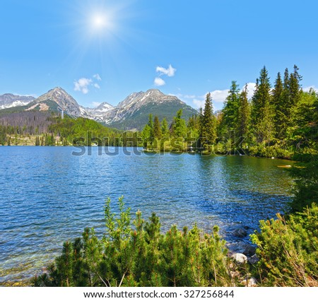 Strbske Pleso spring view with mountain lake  (Slovakia) and sunshine in blue sky/ - stock photo