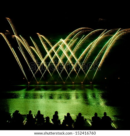 Streaks of Golden Fireworks with people watching by a lake - stock photo