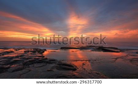 Streaks of orange red light colour the sky and reflect in the water at the rocks of North Curl Curl  Australia - stock photo