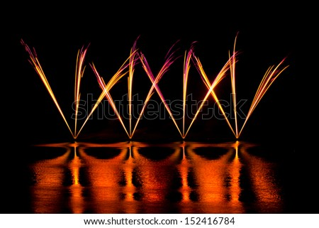 Streaks of Pink and Yellow Fireworks reflected in a lake - stock photo
