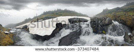 Stream among melting snow under the peak of Hoverla, stormy clean water feeds the waterfall and the river Prut on the background of the mountain slopes of the Carpathian Mountains