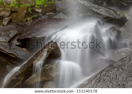 Stream flowing in motion over rocks. Natural background  - stock photo