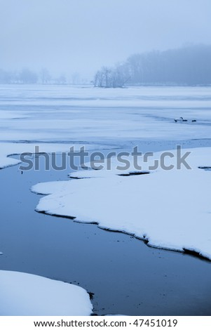Stream flowing through frozen lake