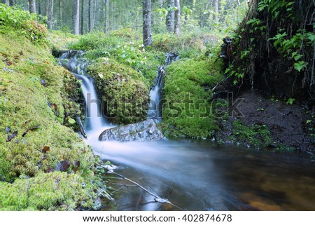 Stream in the woods, springtime photographed with long exposure, dalarna, sweden