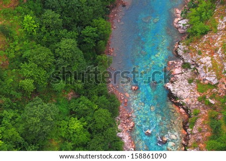 Stream of blue water flowing at the bottom of a canyon - stock photo