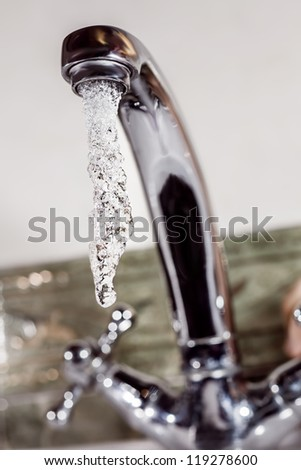 Stream of cold water flows from the metal tap - stock photo