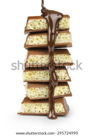 stream of hot chocolate pouring into pieces of milk and white chocolate on a white background - stock photo