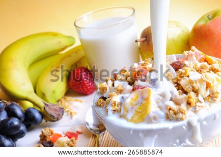 Stream of milk falling into a bowl of cereal and fruits on a table with fruits and glass of milk background - stock photo