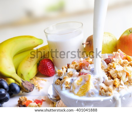 Stream of milk falling into a bowl of cereal and fruits on a table with fruits and glass of milk background in the kitchen. Elevated view - stock photo