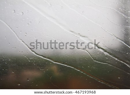 Stream of water in heavy rain. Raindrops on window pane. Blur effect.