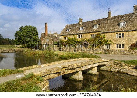 Stream running through the picturesque Cotswold village of Lower Slaughter, Gloucestershire, England, with footbridge and mill - stock photo