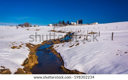 Stream through a snow covered farm field in rural Lancaster County, Maryland. - stock photo