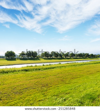 Stream trickled through pasture under blue sky and white cloud, Dong Shan River, Yilan City, Taiwan  - stock photo