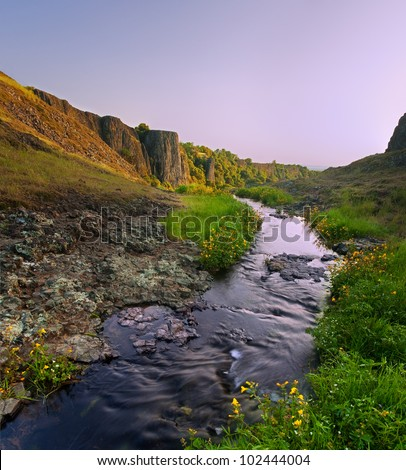 Stream which feeds beautiful Phantom Falls waterfall and surrounding cliffs, North Table Mountain Ecological Preserve, near Chico California, at sunset - stock photo