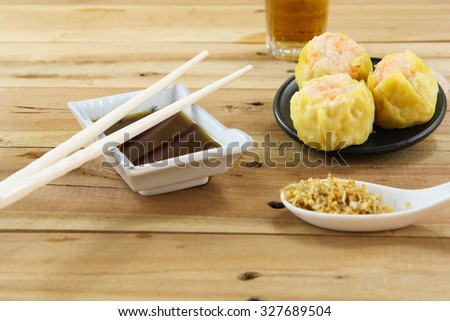 Streamed Chinese Dumpling with black sauce dip and chopsticks - stock photo
