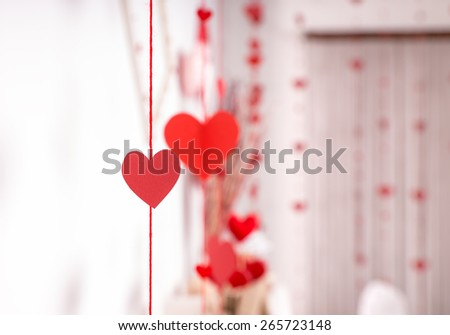 Streamers of red hearts hanging on ribbons decorating a wedding venue and reception symbolising love and romance - stock photo