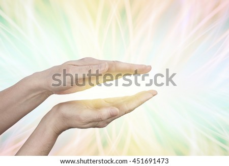 Streaming Golden Energy - female hands held in parallel position with a golden glow between on a multicolored radiating light streaming outwards with copy space