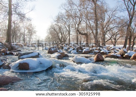 Streaming water in a small river at early springtime. Spring scene.  Mountain landscape with a frozen creek - stock photo