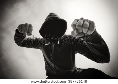 Street agression, being punched and mugged by aggressive violent man in hooded jacket on street, victim's pov perspective, monochromatic black and white image. - stock photo