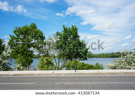 Street and sidewalk with a lake in the background - stock photo