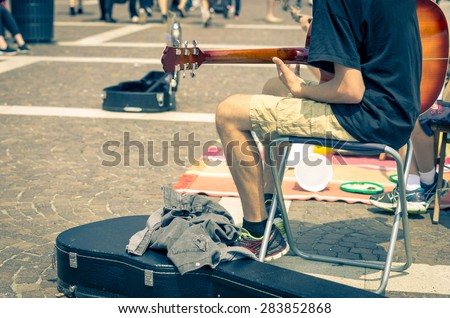 Street artist plays guitar - art, lifestyle and music concept - stock photo