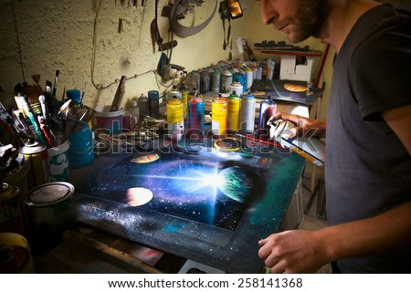 Street artist working in his studio creating color spray painting. - stock photo