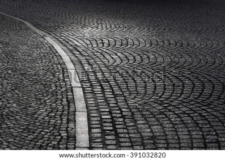 Street at night. Black and white photo of paving stone / slabs / cobbles on sidewalk and carriageway in backlight. Traditional European construction material. Old town. Urban scene. - stock photo
