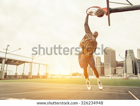 Street basketball player performing power slum dunk. Manhattan and New york city in the background - stock photo