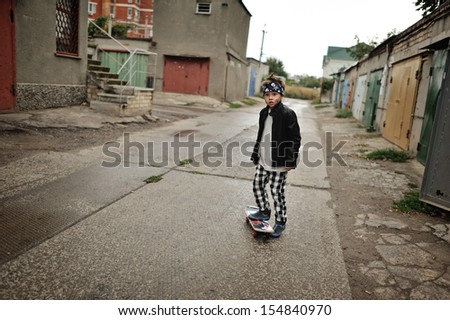 street boy in a black jacket and trousers in a cage riding a skateboard
