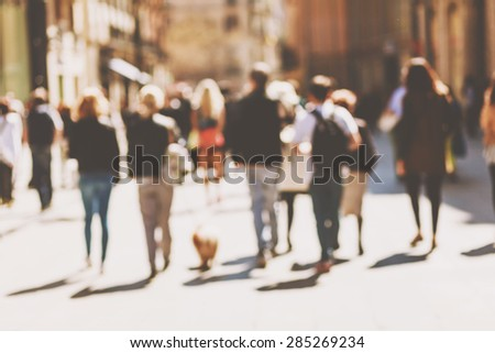 Street cafe in Barcelona with square metal table and wicker chairs on the background of blurred street with people - stock photo
