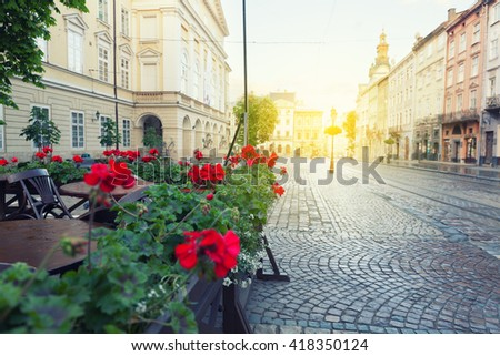 Street cafe terrace with tables and flowers in European city