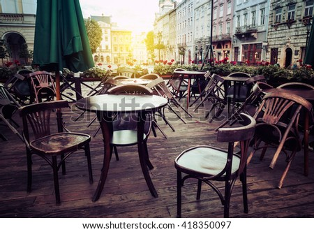 Street cafe terrace with wooden tables and chairs in European city