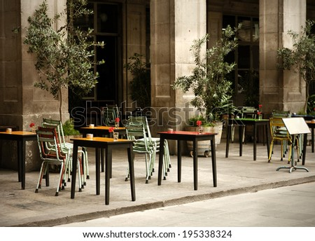 street cafe with colorful tables and chairs, with retro toning effect, in soft focus - stock photo