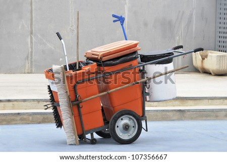 Street cleaner tools in an orange cart. Street cleaning service