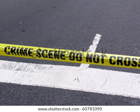 Street crime scene with police line do not cross yellow warning tape above road