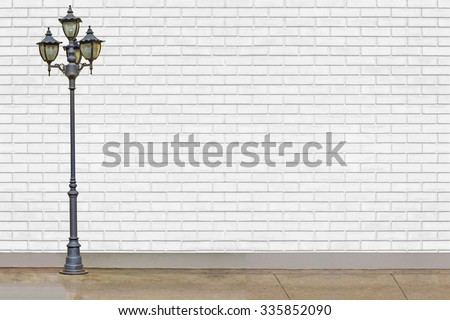 street electric lamp post at white brick wall - stock photo