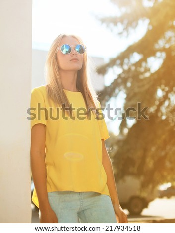Street fashion and people - concept, stylish pretty woman in sunglasses posing in the city - stock photo