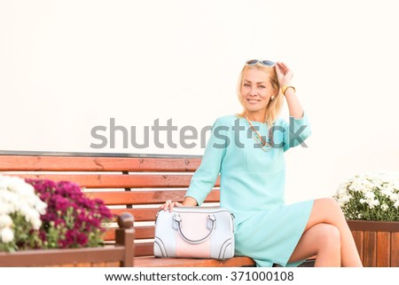 Street fashion beautiful woman sitting on a bench and smiling at camera - stock photo