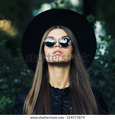Street fashion concept - closeup portrait of a pretty girl. Wearing hat and leather jacket, round sunglasses. Autumn woman. Artsy bohemian rock style. Fall fashion. Toned style instagram filters - stock photo