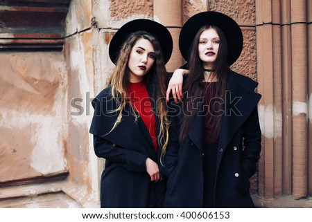 Street fashion concept - closeup portrait of a pretty models. Lifestyle portrait of girls makes funny grimaces on camera. Two women bloggers posing outdoor. Boho style. Toned style instagram filters