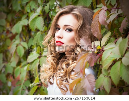 Street fashion concept. Fashion portrait of beautiful brunette with curly hair in trendy casual clothes posing over the wall of wild grapes. Vogue style. - stock photo