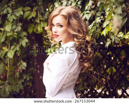 Street fashion concept. Fashion portrait of beautiful brunette with curly hair in trendy casual clothes posing over the wall of wild grapes. Vogue style. Outdoor shot - stock photo