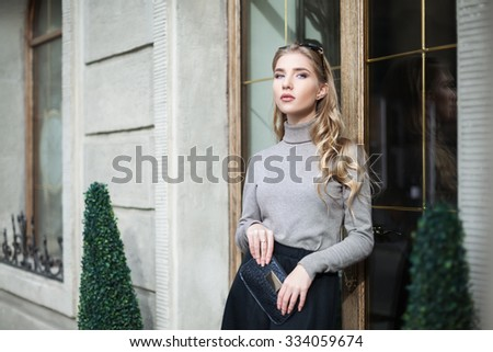 Street fashion concept: portrait of young beautiful elegant woman standing near the door - stock photo