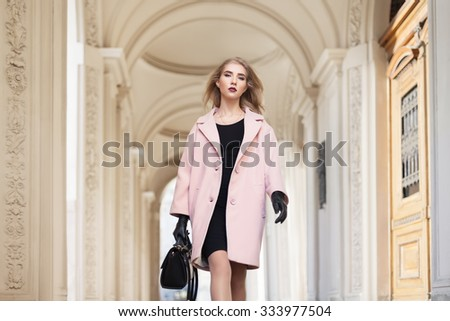 Street fashion concept: portrait of young beautiful woman wearing pink coat with handbag walking in the city. Model looking at camera. Old architecture background  - stock photo
